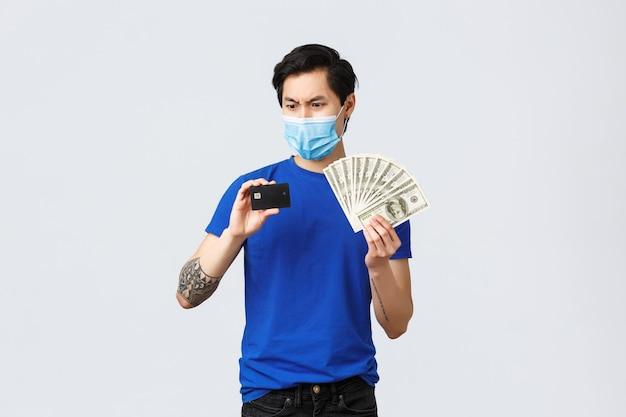 Geld, covid-19, eenvoudig betalings-, investerings- en bankconcept. verwarde en besluiteloze aziatische man die gefrustreerd naar creditcard staart terwijl hij deze vasthoudt en contant geld, begrijpt het niet, draagt een medisch masker