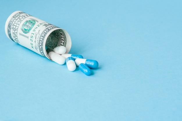 Geld dollar samengevouwen met pillen stroomt geïsoleerd op blauwe achtergrond, hoge kosten van dure medicatie concept. kopieer ruimte.