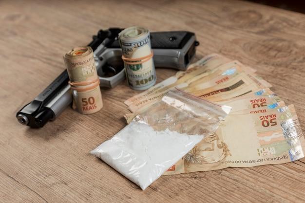 Geld, drugs en een pistool op een houten tafel