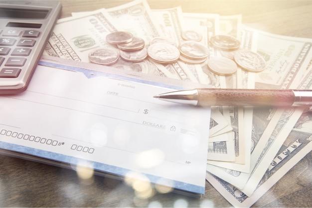 Geld en chequeboek met pen, rekenmachine op tafel