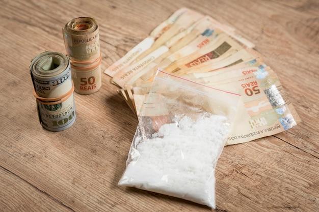 Geld en drugs op een houten tafel