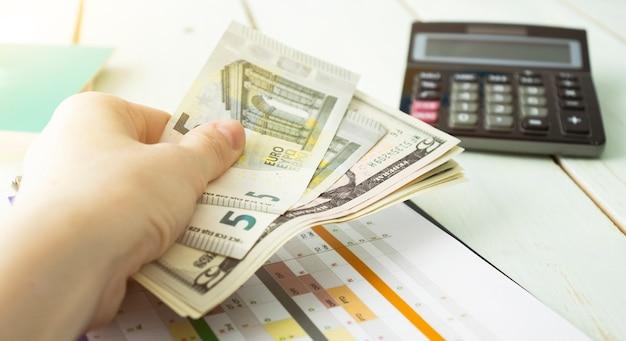 Geld en financiën concept - close-up van vrouw tot een kom gevormde handen die euromunten tonen