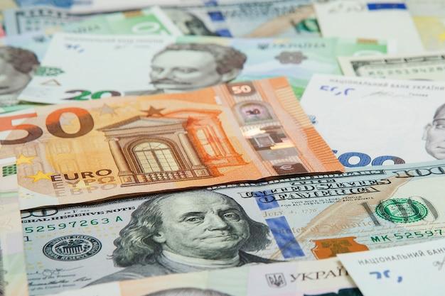 Geld en financiënconcept. honderd dollar nieuwe rekening op kleurrijke abstracte achtergrond van oekraïense, amerikaanse en euro nationale valuta bankbiljetten