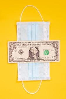 Geld en maskeren gele achtergrond, economische problemen door covid-19