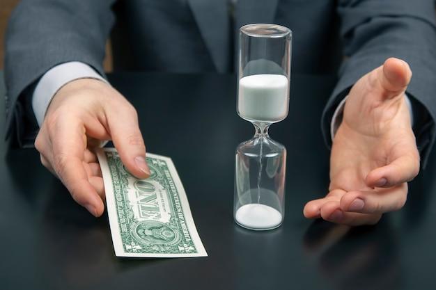 Geld en zandloper op de ruimte van een zakenman. verdeling van tijd voor werk. tijd om beslissingen te nemen. menselijke beloning