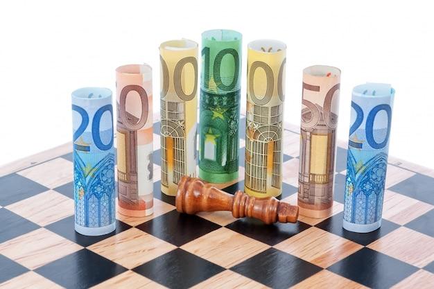 Geld euro op schaakbord en verslagen figuur van de koning.