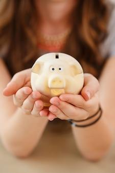 Geld, financiën. vrouw met piggy