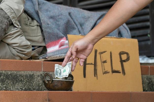 Geld geven aan dakloze mannen langs de kant van de weg.