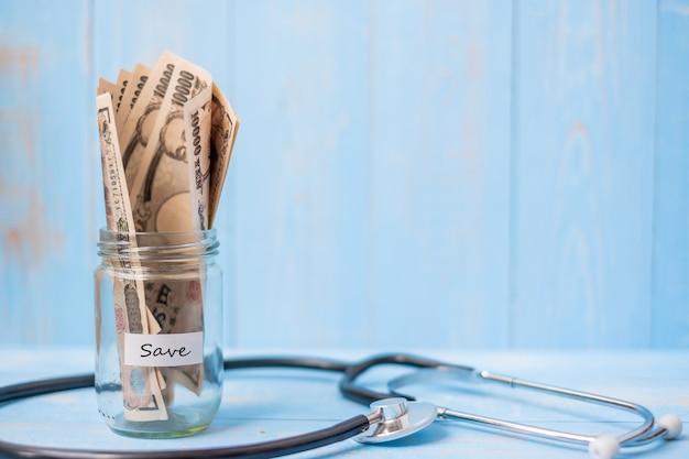 Geld glazen pot en cardiologie stethoscoop