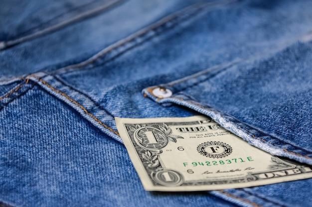 Geld in achterblauwe jeanszak het denimtextuur als achtergrond.