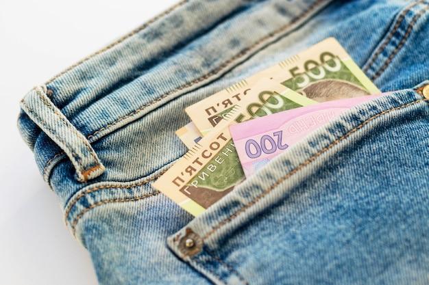 Geld in de achterzak van de spijkerbroek. denim textuur achtergrond. oekraïense vijf en tweehonderd hryvnia. nationale bankbiljetten. financiën, economie en mode concept.