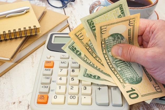 Geld in de hand naast een rekenmachine en kantoorbenodigdheden. financieel begrip.