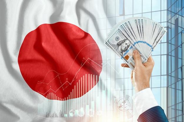 Geld in de hand van een man tegen de achtergrond van de vlag van japan