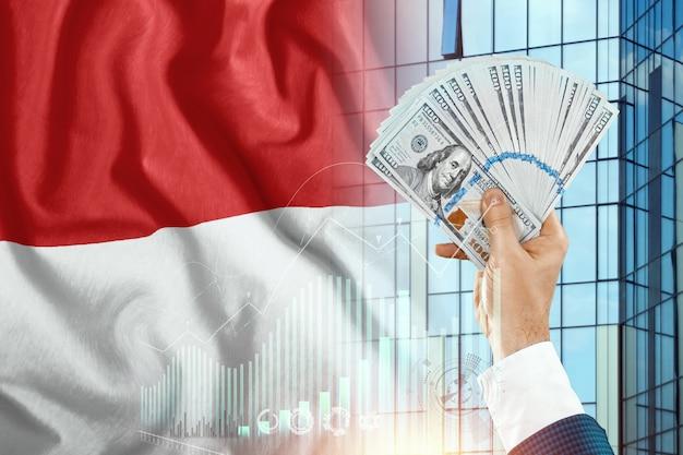 Geld in de hand van een man tegen de achtergrond van de vlag van monaco