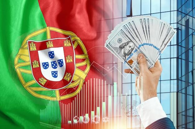 Geld in de hand van een man tegen de achtergrond van de vlag van portugal