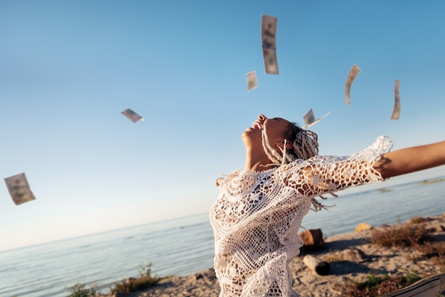 Geld in de lucht. succesvolle welvarende freelancer met witte dreadlocks die haar geld in de lucht gooit