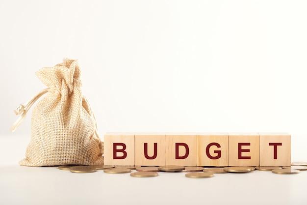 Geld jaarlijkse begroting concept. geldzak en houten kubusblok met woord budget op munten.