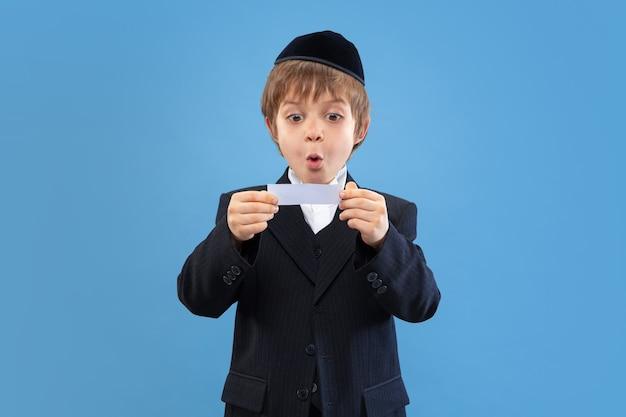 Geld krijgen. portret van een jonge orthodoxe joodse jongen geïsoleerd op blauwe muur. purim, zaken, festival, vakantie, jeugd, viering pesach of pesach, jodendom, religieconcept.