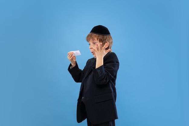 Geld krijgen. portret van een jonge orthodoxe joodse jongen geïsoleerd op blauwe studio muur.