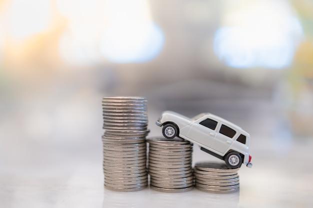 Geld, lenen en sparen. sluit omhoog van wit miniatuur miniautostuk speelgoed bovenop rij van stapel zilveren muntstukken.