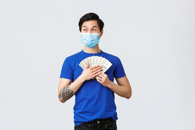 Geld, levensstijl, verzekeringen en investeringsconcept. dromerige, gelukkige aziatische man die contant geld vasthoudt en denkt wat erop te kopen, glimlachend wegkijkt, medisch masker draagt, grijze achtergrond