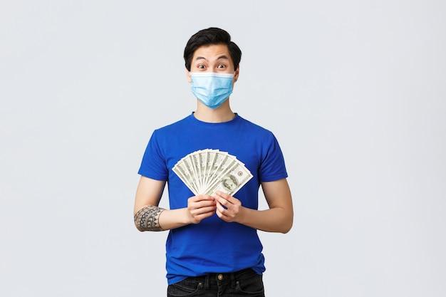 Geld, levensstijl, verzekeringen en investeringsconcept. verrast opgewonden aziatische man won loterij, verdiende veel geld, liet dollars zien en glimlachte verbaasd, met medisch masker