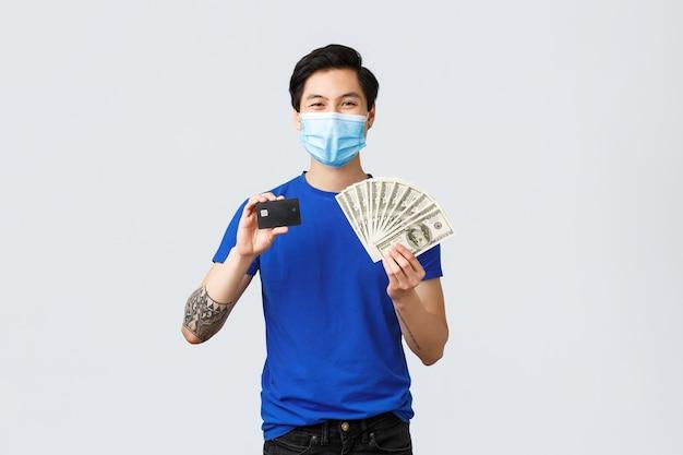 Geld, levensstijl, verzekeringen en investeringsconcept. zelfverzekerde glimlachende aziatische man raadt aan bank- en contactloze betalingen te gebruiken, creditcard en contante dollars te tonen, medisch masker te dragen