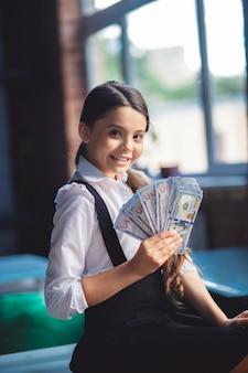 Geld. meisje dat in wit overhemd dollars houdt en gelukkig kijkt