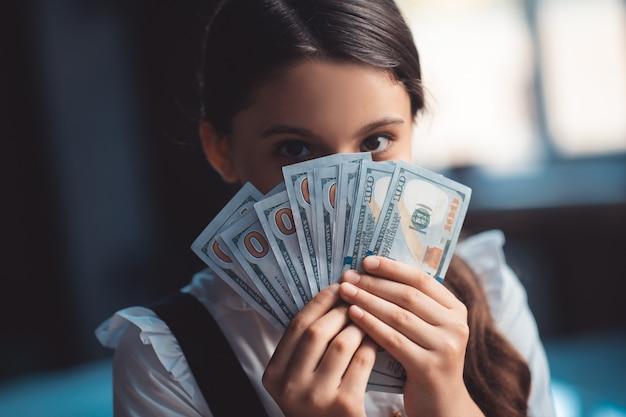 Geld. meisje dollars houden en haar gezicht sluiten