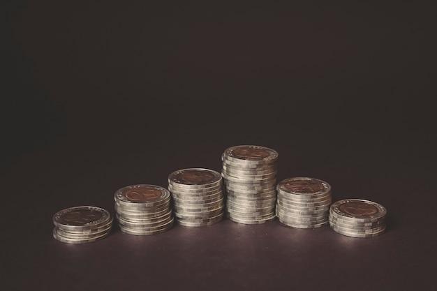 Geld munt op elke lijn stijgt op donkere achtergrond. zakelijk geld besparen concept voor financiële boekhouding. beurs. bedrijfsgroei, schaven en strategieconcept. digitale marketing.