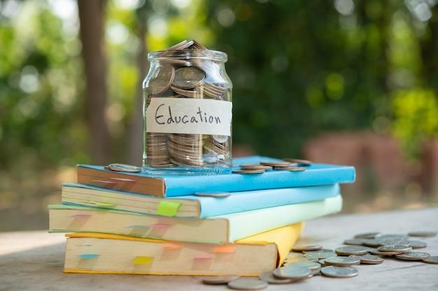 Geld munten besparing in glazen fles voor concept investeringen beleggingsfonds financiën en zaken, geplaatst op het leerboek. inhoud geld besparen voor onderwijs.