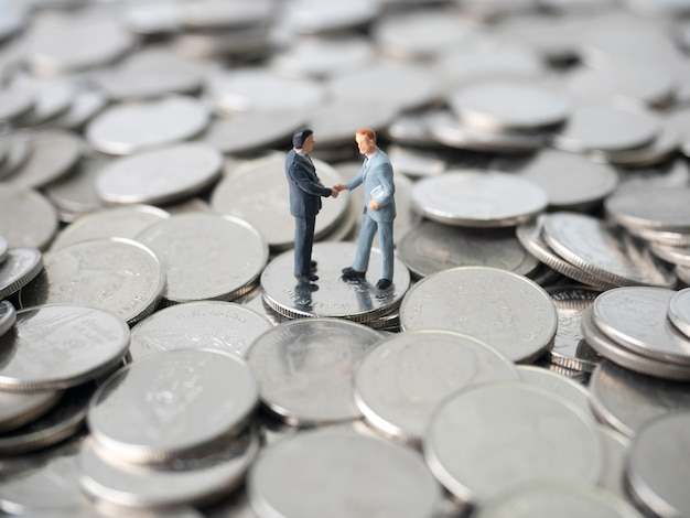 Geld, muntenstapel, twee miniatuurzakenmanhandshaking