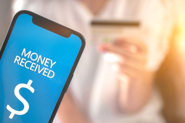 Geld ontvangen scherm en bankcreditcard in vrouwenhand op de achtergrondfoto