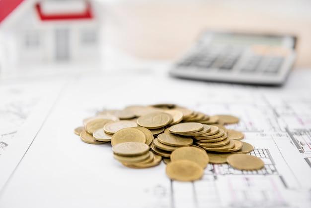Geld op blauwdrukdocument met vaag huismodel en calculator op achtergrond