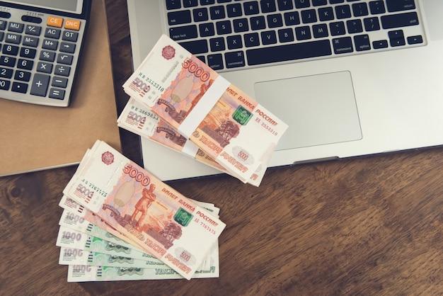 Geld, russische roebelvaluta, op laptopcomputer aan werktafel
