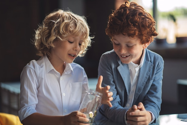 Geld. twee jongens onderzoeken de pot met munten