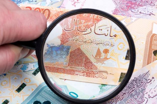 Geld uit qatar in een vergrootglas een zakelijke achtergrond