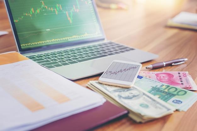 Geld usd dollars, yuan rmb, euro geld op laptop met beurs op scherm.