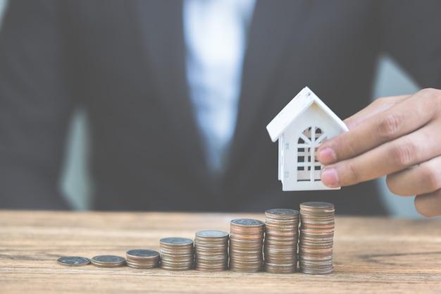 Geld van muntenstapelstijging groeiende groei met model wit huis op houten lijst.