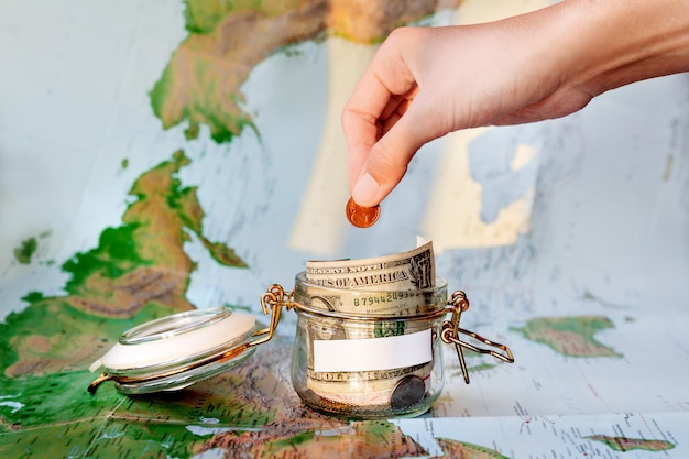 Geld verzamelen voor reizen. glasblik als spaarpot met contante spaargeld (bankbiljetten en munten) op kaart