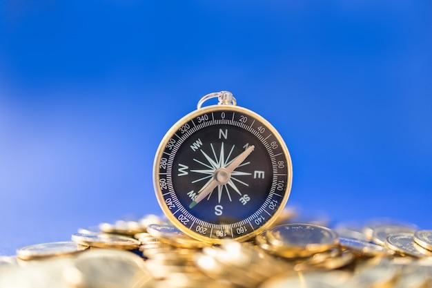 Geld, zaken en richting en planning concept. close-up van kompas op stapel van gouden muntstukken op blauw met exemplaarruimte.
