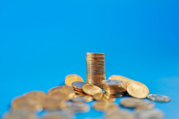Geld, zaken en risicoconcept. close-up van stapel en stapel van gouden muntstukken op blauw met exemplaarruimte.