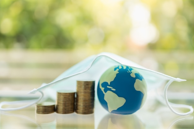 Geld, zaken, gezondheidszorg in cornavirus (covid-19) situatieconcept. mini wereldbal met stapel gouden munten onder chirurgische gezichtsmasker met kopie ruimte.