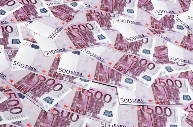 Geldachtergrond die uit paarse vijf honderd euro rekeningen bestaat die over het scherm worden uitgespreid.
