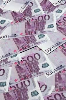 Geldachtergrond die uit paarse vijf honderd euro rekeningen bestaat die over het scherm worden uitgespreid