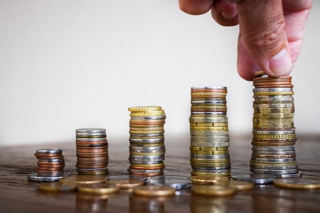 Geldbesparend concept, vooraf gedefinieerd door mannenhand die muntgeld in de stapel zet.