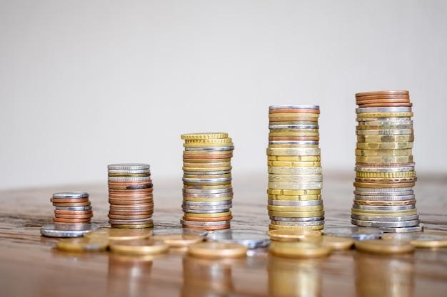 Geldbesparend concept, voorgedefinieerd door de stapel munten die steeds meer georganiseerd worden.