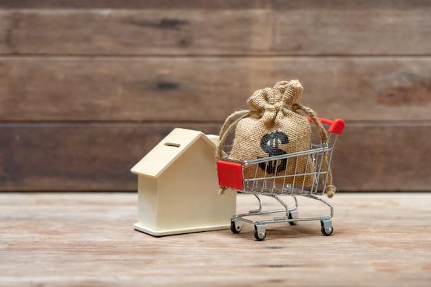 Geldbesparende concept van het verzamelen van munten (thaise geld) in een winkelwagentje op aard.