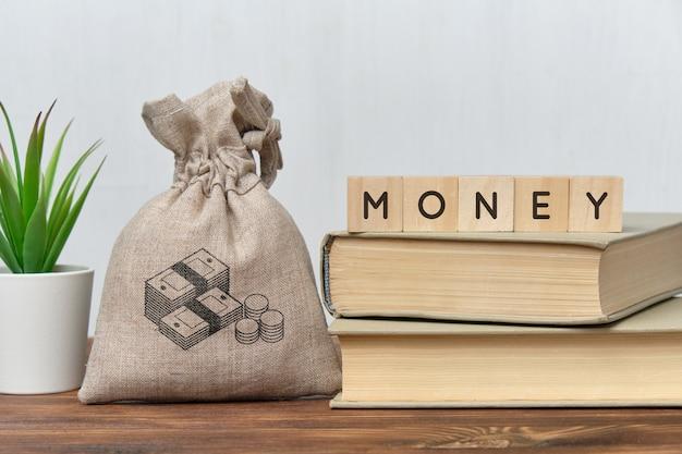 Geldconcept met een zak geld en boeken.