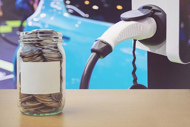 Geldfles met muntstukken, die de achtergrond van een elektrische autobatterij laden